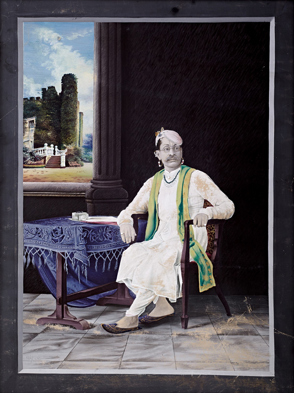Govardhanlalji seated on European-style chair with hand resting on a table