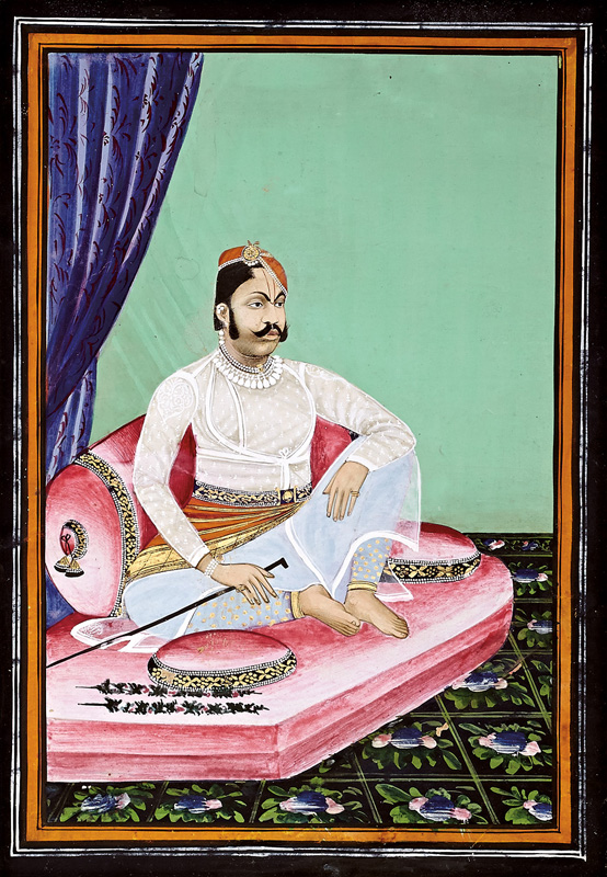 Govardhanlalji sitting on a pink mattress in traditional style